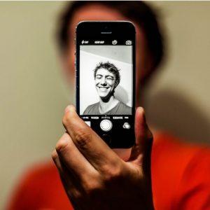 Auf dem Foto macht eine Person ein Selfie. Der Bildschirm des Handys ist im Vordergrund